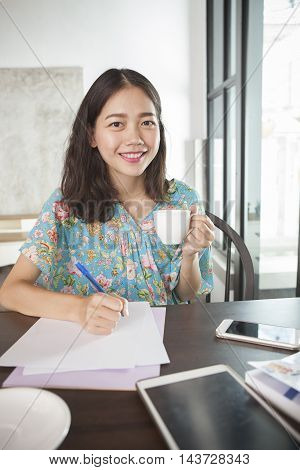 asian woman writing pen on white paper and hot beverage cup in hand smiling face happiness emotion