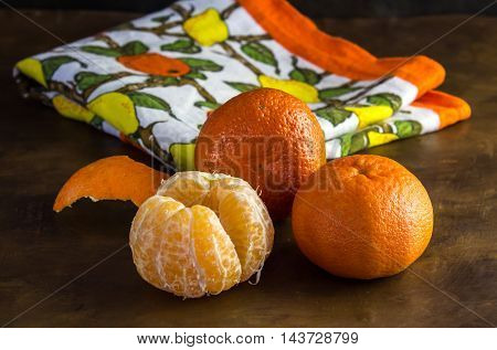Whole and peeled tangerines and kitchen cloth in background
