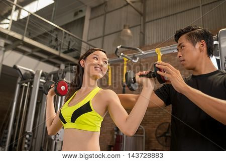 Vietnamese young people exercising in gym with barbell