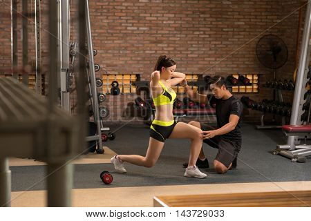Pretty young Asian woman doing lunges in gym
