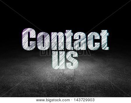 Marketing concept: Glowing text Contact Us in grunge dark room with Dirty Floor, black background