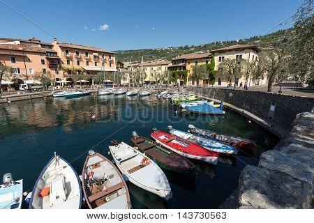 TORRI DEL BENACO, ITALY - MAY 4, 2016: Fishing boats in the small harbor of Torri del Benaco. Garda Lake. Italy