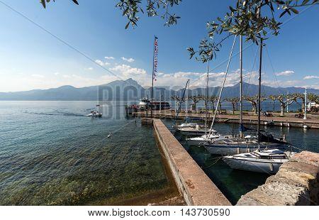 TORRI DEL BENACO, ITALY - MAY 4, 2016: boats in the small harbor of Torri del Benaco. Garda Lake. Italy