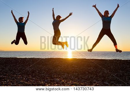 Silhouette of jolly Woman jumping high in three different positions on Ocean Beach with Sunrise on background