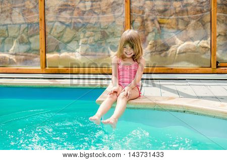 happy little girl sitting by the pool and having fun in the water feet