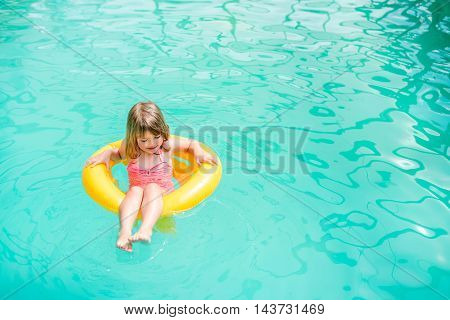 Little girl floating in the pool to rescue circle yellow. Space for text