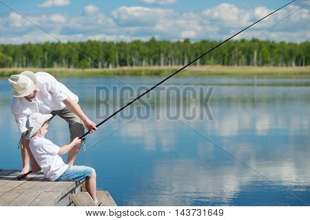 Dad and son caught the fish and pull it
