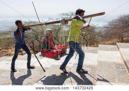 Palitana, India - March 6, 2016: Unidentified workers, carry pilgrims to the Jain temples on top of Mount Satrunjaya near Palitana, Gujarat, India.