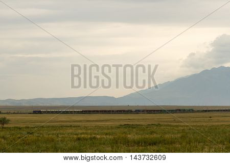 freight train in the steppes of Kazakhstan mountains in the background