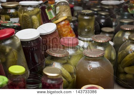 A bunch of canned jars with assorted vegetables stored on a dump cellar closeup indoor shot