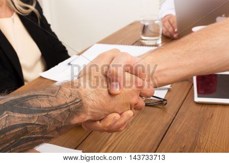Business handshake at office corporate meeting, contract conclusion and successful agreement concept. Closeup of modern hipster businessman and other man's hands meet at wooden table background.