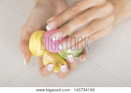 Girl holding colorful macarons in hands with french manicure