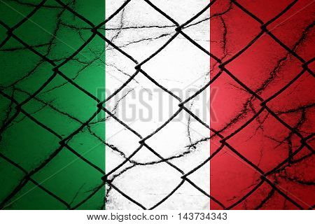 Italian flag, cracks and fence - Refugee crisis concept