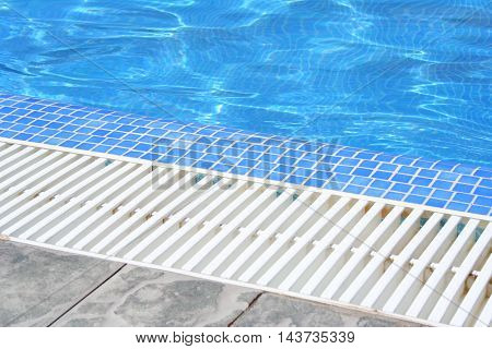 Swimming pool white grating grille with clear blue water and grey tiles. Summer picture detail.