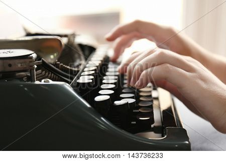 Woman typing on the typewriter, closeup