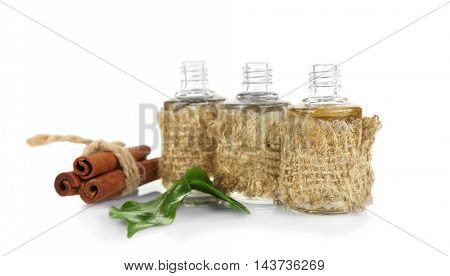 Tea oil in glass bottles and cinnamon, isolated on white