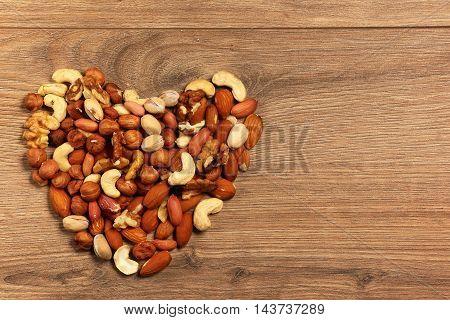 Nuts arranged in heart shape on wooden background