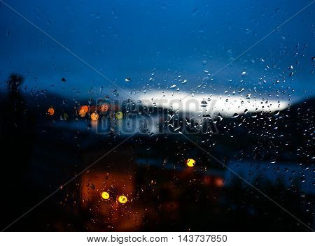 window after rain at sunset, raindrops, lights