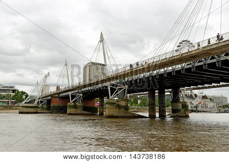 LONDON UK - JULY 8 2016: Hungerford Bridge and Golden Jubilee Bridges. The footbridges either side were opened in 2002 and named in celebration of the Queen's Golden Jubilee.