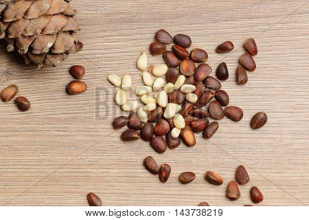 Pine nuts and a pine cone closeup on wooden background