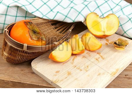 Persimmon yellow color ripe split fruits on wood table
