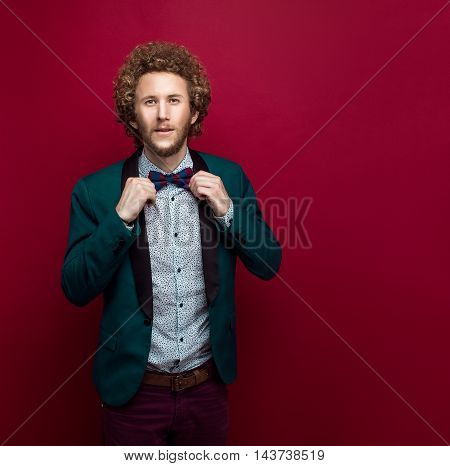 Bearded stylish man with curly hair wearing bow-tie, green jacket. Red background. Isolated