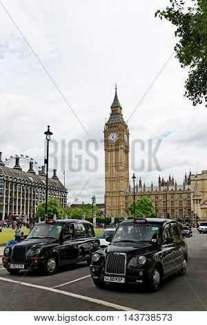 LONDON ENGLAND - JULY 8 2016: Two iconic black cabs in front of Big Ben tower. With 96.3 meters high it is one of the most important attraction and a symbol of London.