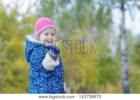 Two years old girl is showing two fingers on her hand at autumn park foliage backdrop