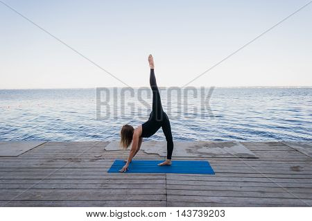 An image of a pretty woman doing yoga at the lake.