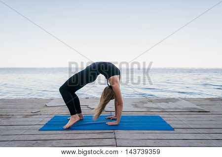 Beautiful sporty fit blond young woman in black sportswear working out outdoors on wooden pontoon on the lake, doing Bridge Pose, standing in Urdhva Dhanurasana, Chakrasana posture, full length.