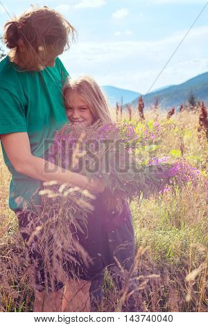 Happy mom and daughter are hugging on alpine meadow among the lush herbs on the background of a blue sky and mountains at sunny day. Toned image.