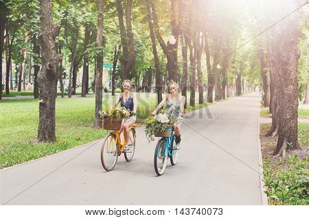 Happy boho chic stylish girls ride together having fun. Beautiful women on bicycles with baskets full of wild flowers. Female friends, youth and happiness, active summer leisure in park concept.