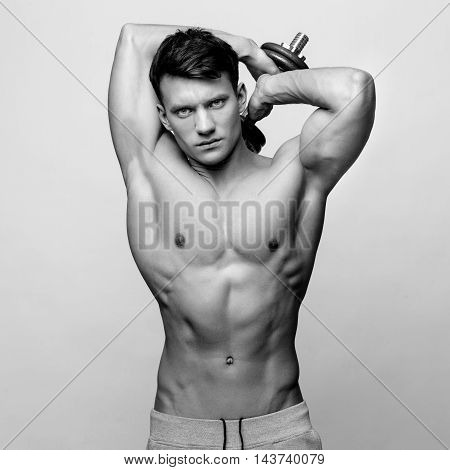Studio shot of Shirtless bodybuilder holding dumbell and showing his muscular arms.