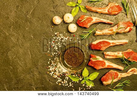 Raw lamb chops with salt, pepper and rosemary over black background. Meat fork near. Top view. With copy space at left