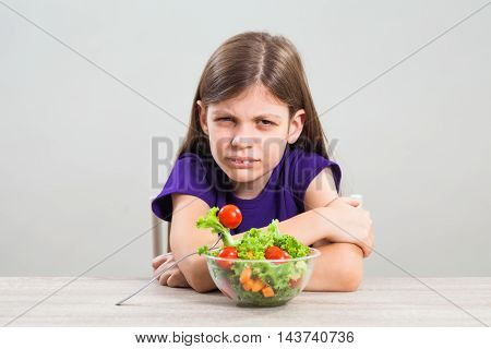 Little girl is unhappy because she does not like to eat salad.