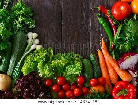 Frame of fresh organic vegetables on wood background. Healthy natural food on rustic wooden table with copy space. Tomato, lettuce, carrot, pepper, zucchini and other cooking ingredients top view
