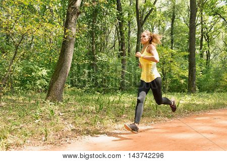 Young woman jogging in park, horizontal image, color image