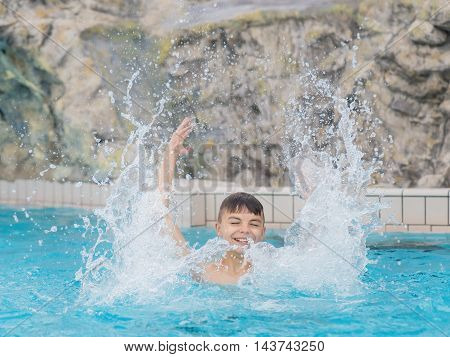 Happy teen boy jumping in the swimming pool at aquapark. Cute child having fun enjoyable time on vacation. He laughing and splashing water.