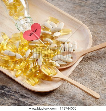 Supplement capsule dish on wooden background with red heart and take care wording.