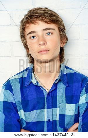Portrait of a teenage boy standing by a white brick wall. Studio shot. Teen fashion.