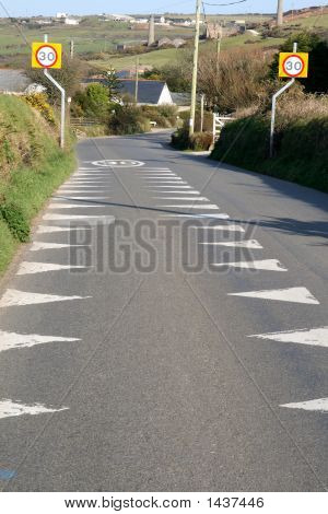 A British Road With 30 Miles Per Hour Sign And Warning Markers.