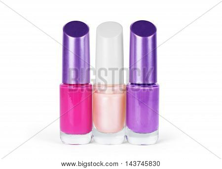 A close up on three bottles of fingernail polish isolated on a white background.