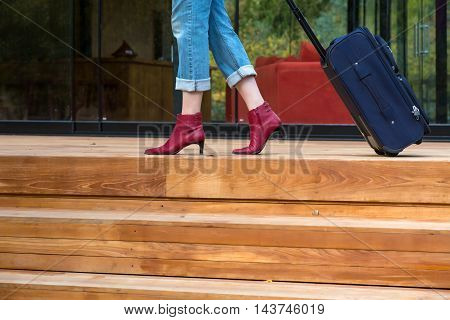Person walking on wooden terrace pulling Travel Suitcase female Legs and Hand casual vacation Clothing red attractive high Heels Shoes and Jeans