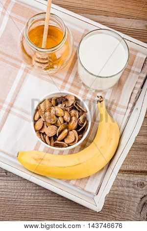 Healthy breakfast concept with oat flakes with banana honey and milk.