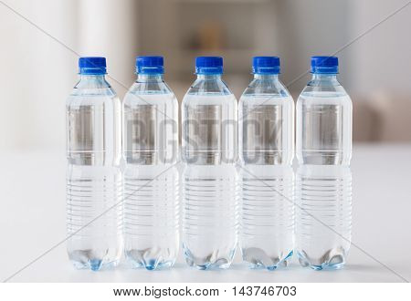 recycling, healthy eating, industry, packing and food storage concept - close up of plastic bottles with pure drinking water on table