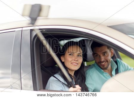 road trip, leisure, couple, technology and people concept - happy man and woman driving in car and taking picture with smartphone selfie stick