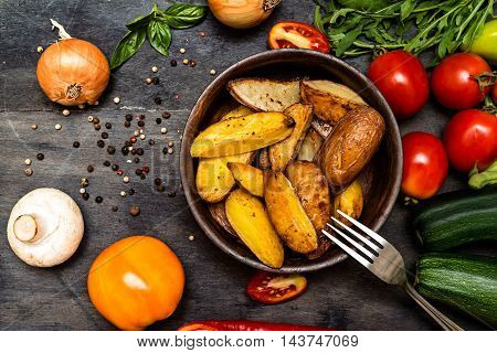 Roasted potatoes with herbs and vegetables on rustic background