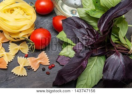 Pasta with basil leaves cherry and spices on dark background