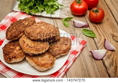 Fried pork burgers with tomatoes on the woodenrustic table. grilled pork cutlets.