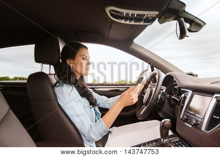 safety, road trip, technology, travel and people concept - woman driving car with smarhphone